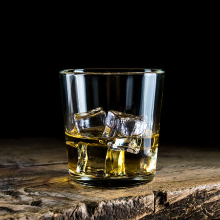 A glass of whiskey with ice cubes on a wooden table and a dark background 免版税图像