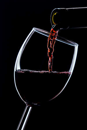 Red wine pours from a bottle into a glass on a dark background 免版税图像