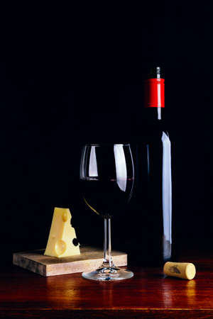 A glass of red wine, a bottle and a piece of cheese on a wooden table and a dark background