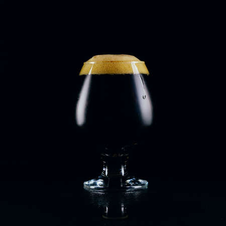 A glass of porter beer on a dark background