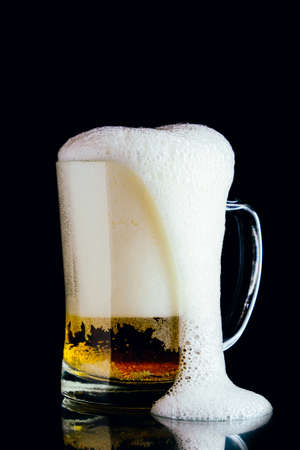 Beer mug with foam on a dark background 免版税图像