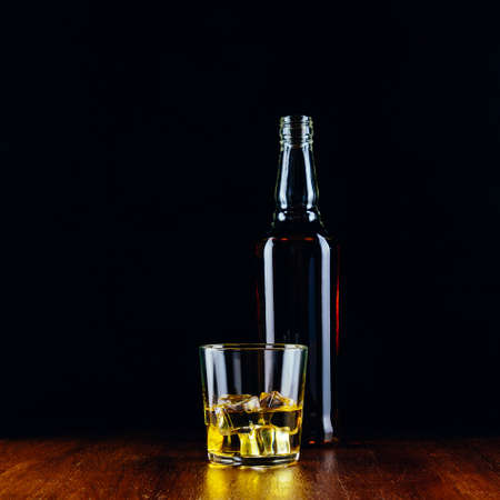 A glass of whiskey with ice cubes and a bottle on a wooden table and a dark background 免版税图像