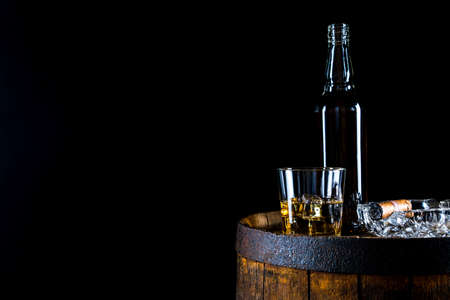 A glass of whiskey and ice cubes and a bottle on an old wooden barrel