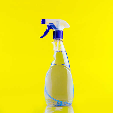 A bottle of cleaner with a white label on a yellow background. Template for text or design