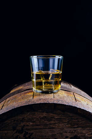 A glass of whiskey and ice cubes on an old wooden barrel 免版税图像