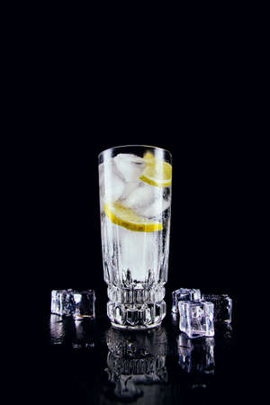 A glass of gin and tonic with lemon and ice cubes on black background