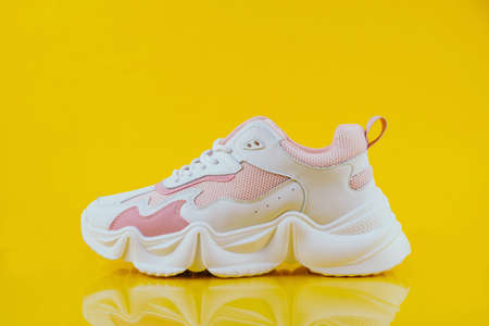 White and pink sports sneakers on an yellow background