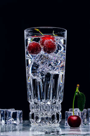 A glass of gin and tonic with cherry and ice cubes on black background