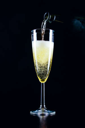 Sparkling wine pours from a bottle into a glass on a dark background 免版税图像