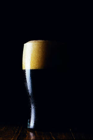 Porter beer mug with foam on a dark background