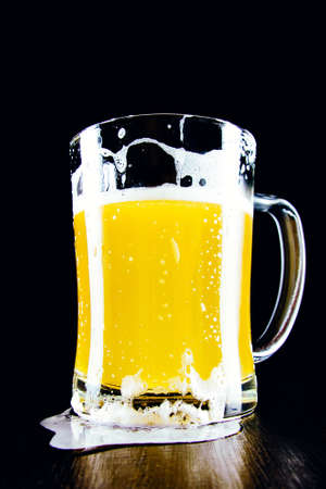 Lager unfiltered beer mug with foam on a dark background 免版税图像