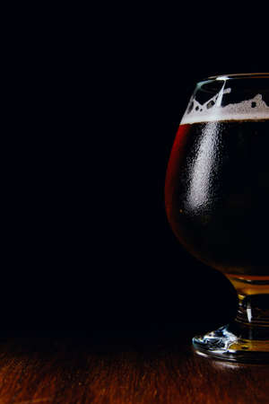 A glass of brown ale on a wooden table and dark background