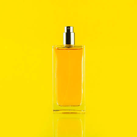 Perfume bottle on a light yellow background 免版税图像