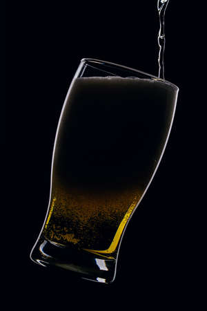 Lager beer pours from a bottle into a glass on a black background