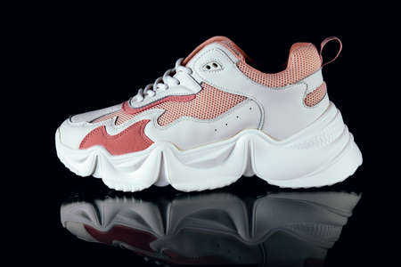 White and pink sports sneakers on an black background