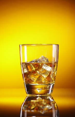 pouring whiskey in glass filled with ice