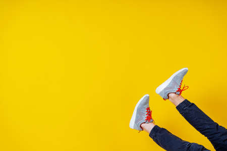 feet sticking out from the bottom in sneakers on a yellow background, red laces, a concept for a fashion blog or magazine, a minimalistic Shoe background, sports