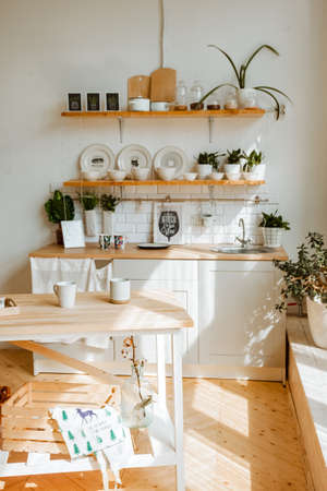 the sun's rays fall on the kitchen set, glare from the sun on the dishes, the interior of the dining area, stylish youth design for bright rooms