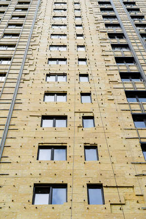 cladding of a multi-storey building with insulation, construction of a house, exterior decoration of a building, multi-storey building, glass wool
