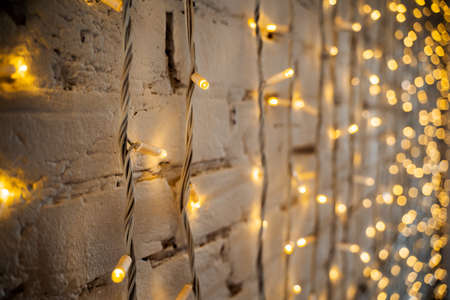 small lights garlands hanging on a white wall, taken in the evening, close-up, macro photography