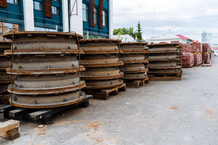 metal manhole covers from the sewer are stacked in a row on the street, road works, construction materials are lying on the asphalt, rusty color, summer day, road repairs