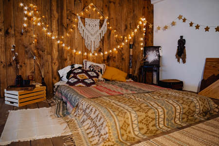 loft room on the second floor in a wooden style with lights, warm colors, interior design, bed on the floor, a cozy place to sleep Foto de archivo