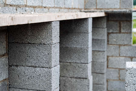cinder blocks of gray concrete are neatly stacked in a pile, slender rows of bricks, material for building a house Фото со стока