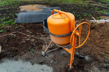 an orange concrete mixer where cement is prepared for construction works stands on the street