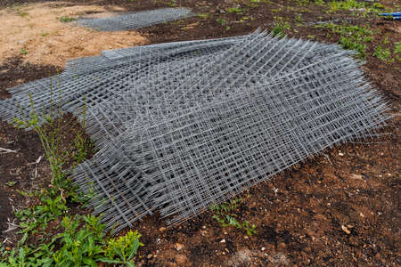 iron grid with square cells for the construction works, a metal grille folded in a pile