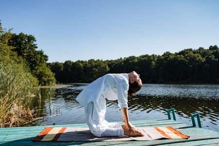 a young girl does yoga on a lake on a Sunny summer day, meditation, relaxing pose, solitude in nature, peace, relaxation, asana, healthy lifestyle, life style, Zen Stock Photo