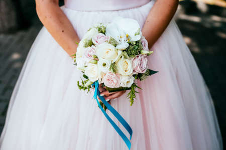 Bridal bouquet, hold the wedding bouquet in your hand, satin ribbons adorn the wedding bouquet of roses, on the background of the brides dress, fresh flowers, made by a florist