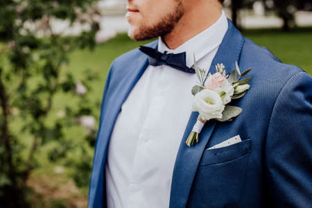 stylish boutonniere on the grooms jacket, wedding day, beautiful flower boutonniere, wedding concept