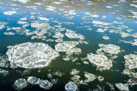 circular ice floes floating in the river begins to freeze