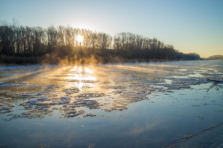 river banks: Sunrise on the banks of the freezing and foggy river