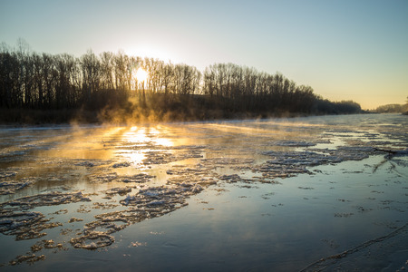riverbank: Sunrise on the banks of the freezing and foggy river