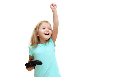 little girl with a gamepad raised her hand up, she won, isolated on white background Stock Photo