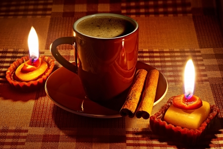 anisetree: Cup of coffee in natural candle lighting  Stock Photo