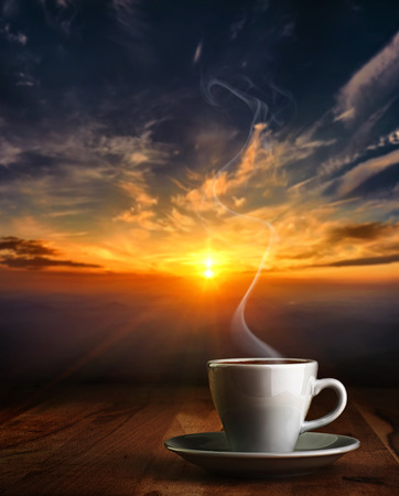 na: Coffee in white pottery cup on old wooden table with blurred image of  sunset or sunrise