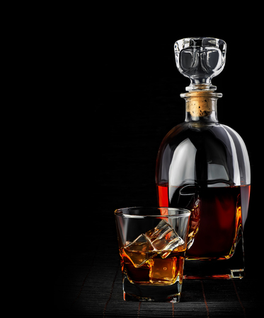 Studio shot of whiskey in a carafe and glass isolated on black photo