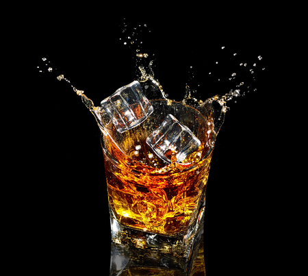 Glass of whiskey with splash on black background Stock Photo