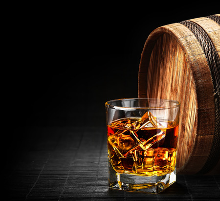whiskey glass: Glass of cognac on the vintage wooden barrel