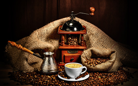 chocolate background: cup of coffee, grinder, turk and coffee beans on brown background