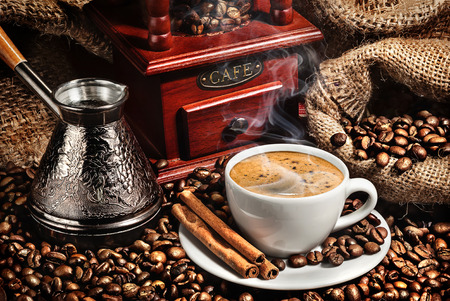 turk: cup of coffee, grinder, turk and coffee beans on brown background