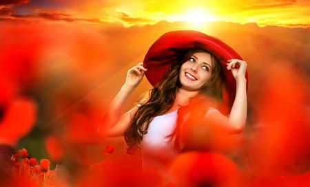 dress blowing in the wind: beautiful girl in a poppy field at sunset