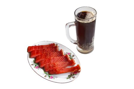 A glass of dark beer and a fish snack on a plate Banco de Imagens