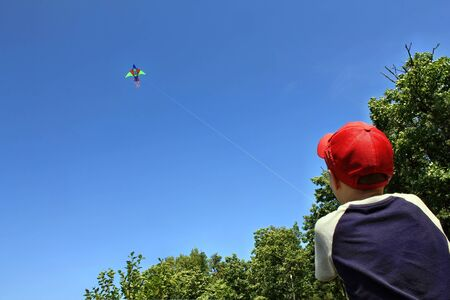 Boy launches a colored kite on a rope Banco de Imagens