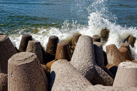 The sea waves are beating against concrete breakwaters