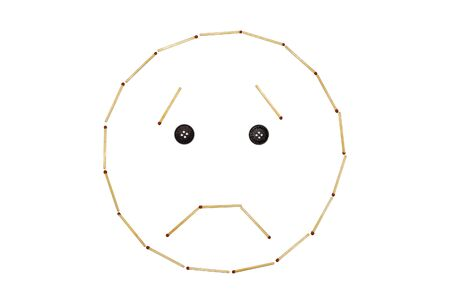 Smiley expressing emotion sorrow is made of matches on a white background