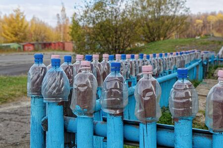 The cut-off bottles are on the fence. Bottles with caps lined up in a row. Blue fence made of plastic bottles. Lots of plastic bottles.