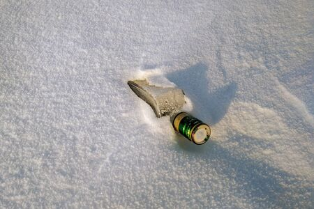 An empty bottle sticks out of a snowdrift. A bottle of alcohol with a green neck.